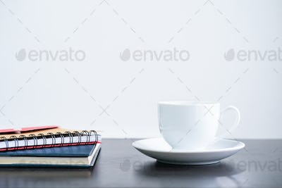 Coffee cup and notebook on desk