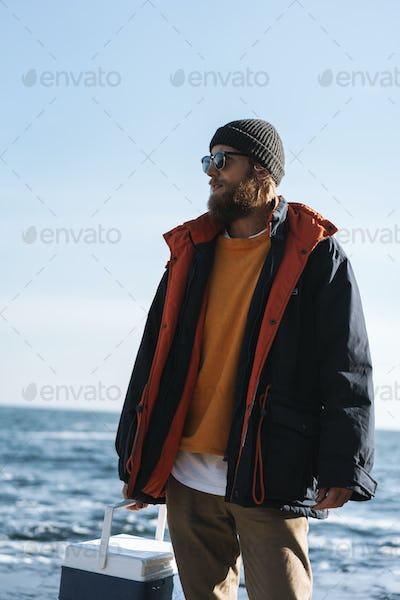 Fisherman wearing coat standing at the seashore