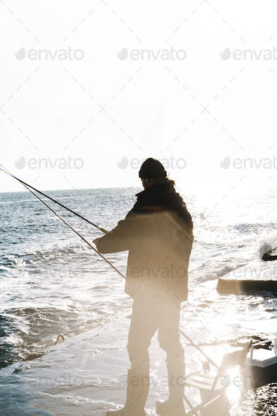 Handsome young man fisherman wearing coat and hat at the seashore.