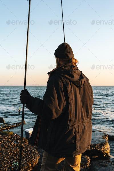 Man fisherman wearing coat standing with a fishing rod