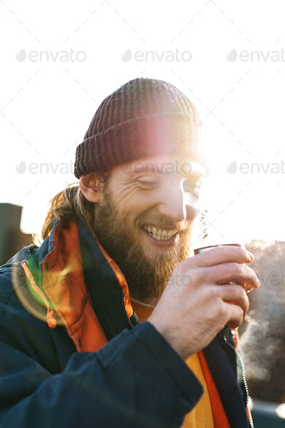 Handsome young man fisherman wearing coat and hat at the seashore drinking hot tea.