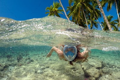Snorkeling near a tropical island. Beautiful girl swims in the water