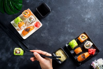 Various Fresh and delicious sushi set on white slate , hand with slate sticks, sauce on light stone