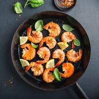 Fried fresh shrimps with spices on black pan