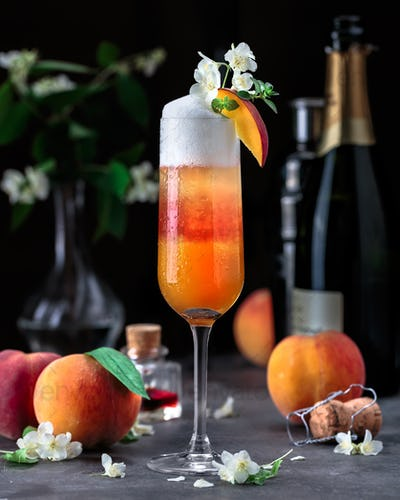 Layered bellini cocktail with peaches on dark background