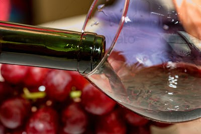 Pouring red wine into the glass against grape