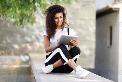 Young black woman in sportswear using digital tablet outdoors