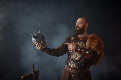 Smiling viking holds enemy's skull in helmet