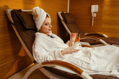 Sexy girl relaxing with cup of coffee in spa chair