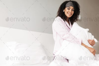 Lady with curly hair sitting on bed and hugging pillow with earphones and eye mask on head at home