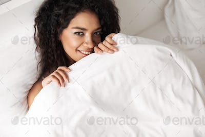 Smiling lady with dark curly hair lying in bed and joyfully looking in camera at home