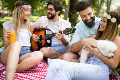 Happy young friends having picnic in the park