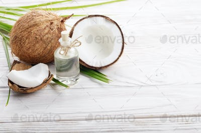 Coconut oil in glass jar and shell pieces on white wooden table