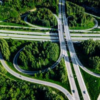 Aerial view of highway and overpass with green woods in Finland.