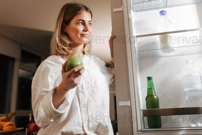 Smiling lady standing on kitchen at night and looking in open fridge holding green apple in hand