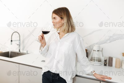 Young lady standing with glass of red wine in hand and dreamily looking aside at home