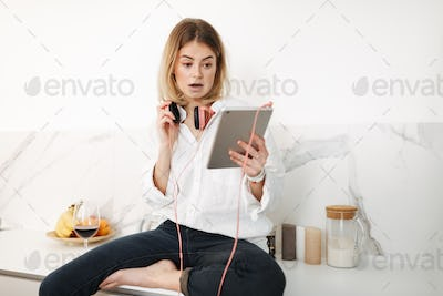 Amazed lady in headphones sitting on kitchen counter with tablet in hands and glass of wine at home