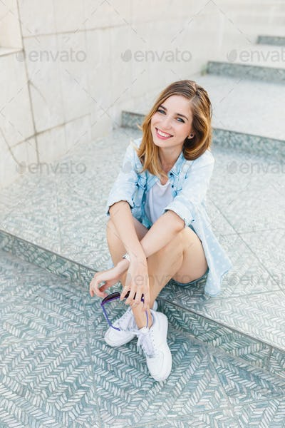 Portrait of a happy young Caucasian woman sitting on light gray steps smiling.
