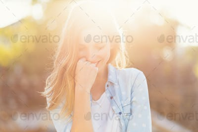 Gorgeous girl with a beautiful smile and sunrays reflected on her happy face