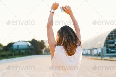 Joyful girl dancing in the street on a sunny day holding hands up
