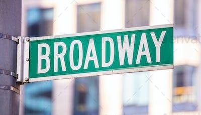 Broadway road sign. Blur buildings facade background, Manhattan downtown