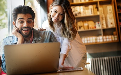 Couple have fun while looking on laptop at cafe