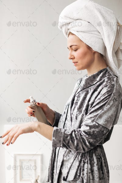 Beautiful lady in velvet robe standing with towel on head and cream in hand at home