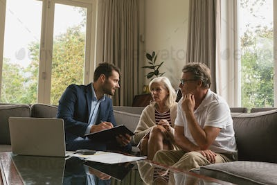 Active senior Caucasian couple discussing with real estate agent over documents