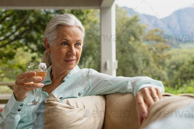 Front view of thoughtful active senior Caucasian woman having champagne in the porch at home