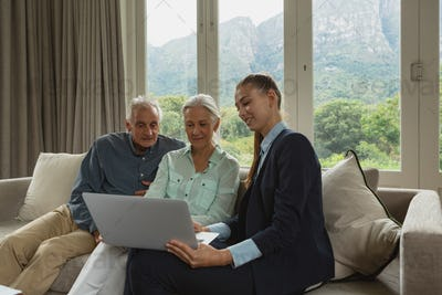 Active senior Caucasian couple discussing with real estate agent over laptop in living room