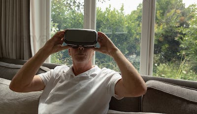 Active senior Caucasian man using virtual reality headset on sofa in a comfortable home