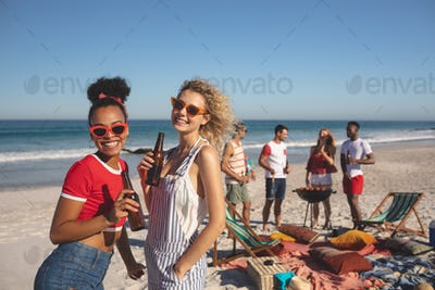 Front view of two diverse friends have beer while diverse friends making a barbecue on the beach