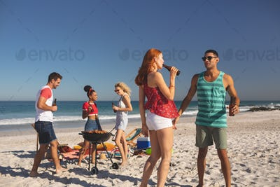 Front view of group of happy diverse friends having fun while having beer on the beach