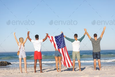 Rear view of diverse friends standing together with American flag and raising hands on the beach