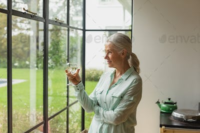 Side view of thoughtful active senior Caucasian woman having champagne at home
