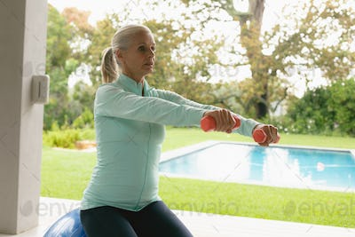 Side view of determined active senior Caucasian woman exercising with dumbbell in porch at home