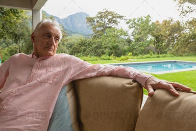 Front view of thoughtful active senior Caucasian man relaxing on sofa in the porch at home