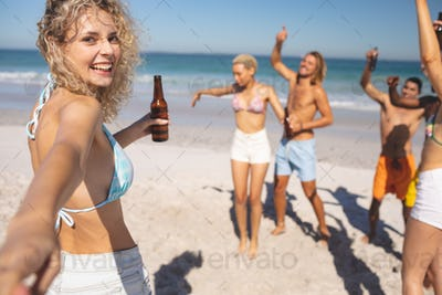 Front view of group of young diverse friends having fun together on the beach