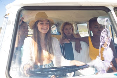 Front view of young group of diverse female friends having fun in a camper van
