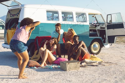 Young Caucasian woman taking pictures of her friends with digital camera near camper van at beach