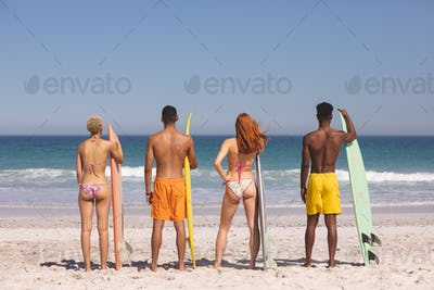 Rear view of diverse friends standing together with surfboard on the beach