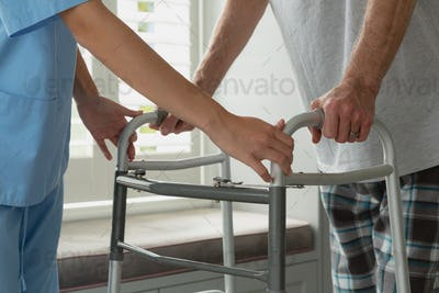 Mid section of Caucasian female doctor helping active senior man to walk with walker at home