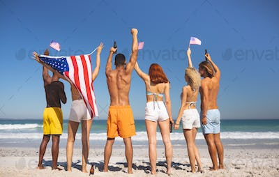 Rear view of diverse friends raising their hands on the beach while holding american flag