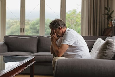 Sad active senior Caucasian man covering his face with hands while sitting on sofa