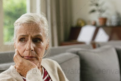 Tensed active senior Caucasian woman with hand on face sitting on sofa