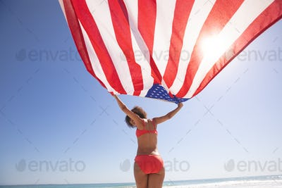 Low angle view of African american woman in bikini holding american flag on the beach
