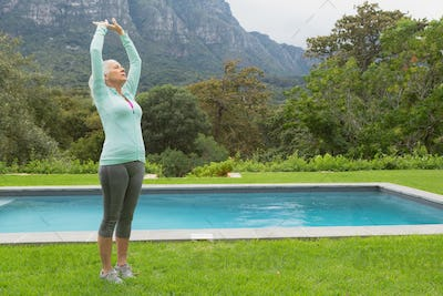 Side view of active senior Caucasian woman exercising near poolside in the backyard of home