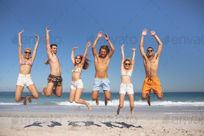 Front view of group of young diverse friends jumping together on the beach