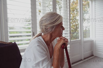 Active senior Caucasian woman leaning on walking cane and looking away in a comfortable home