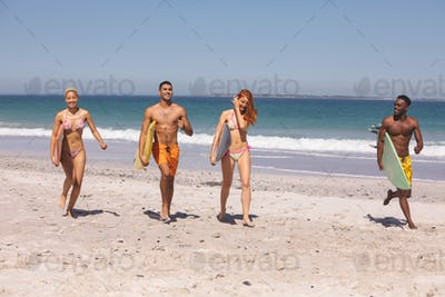 Front view of group of young diverse friends walking together with surfboard on the beach